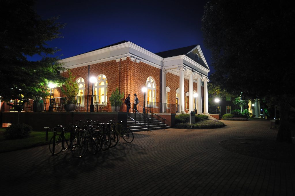 Hege Library building at night. It is lit up by streetlamps and has a dark blue sky behind it.