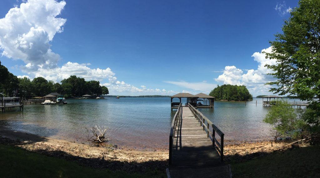 A panoramic picture of a lake with a dock in summer