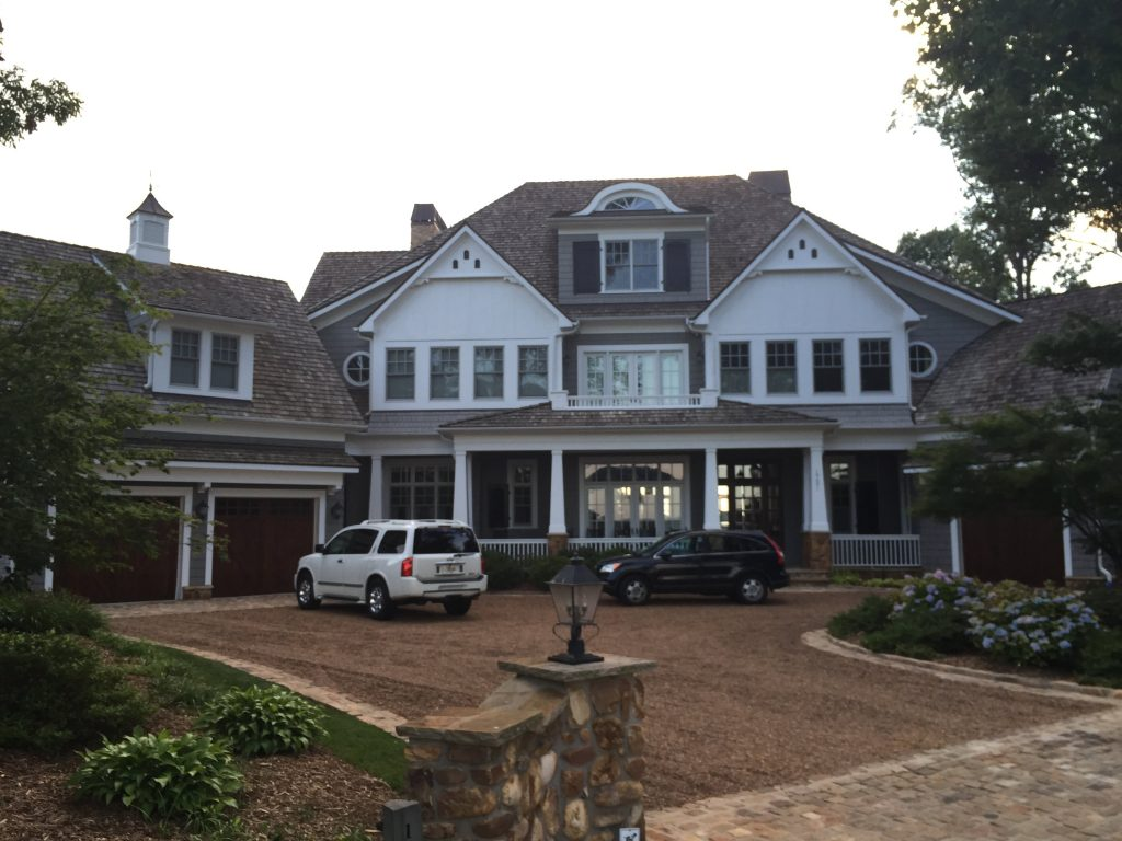 A picture of a really big fancy house with cars in a drive way in front